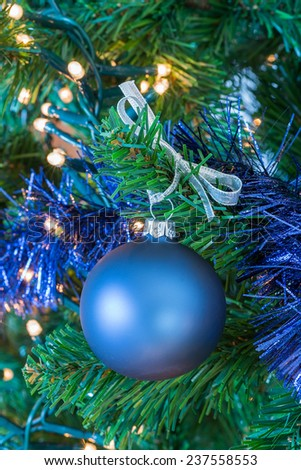 Blue Christmas ball hanging in Christmas tree - stock photo