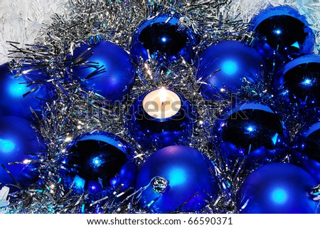 Blue Christmas baubles and a candle among tinsel - stock photo