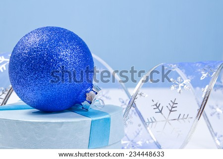 Blue Christmas Decoration: a ball, curved ribbon with snowflakes on a blue background with copy space for text - stock photo