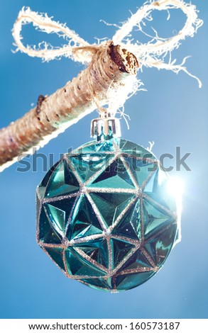 Blue Christmas ornament  highlighted with a bright light. Hanging from a birch tree branch. - stock photo
