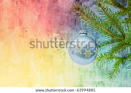 blue christmas ornament on christmas tree with rainbow grunge background - stock photo