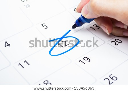 Blue circle. Mark on the calendar at 12. - stock photo
