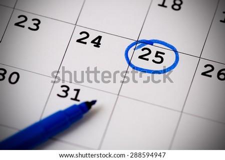 Blue circle. Mark on the calendar at 25. - stock photo