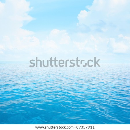 Blue clear sea with waves and sky with fluffy clouds - stock photo