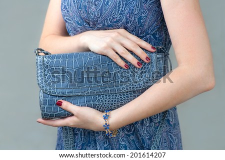 Blue closed clutch in womens hands. Fashion trendy hand bag - stock photo