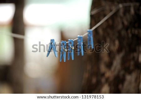 blue clothes pins with wedding rings hanging on rope - stock photo