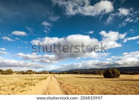 Blue clouded sky over farm field - stock photo