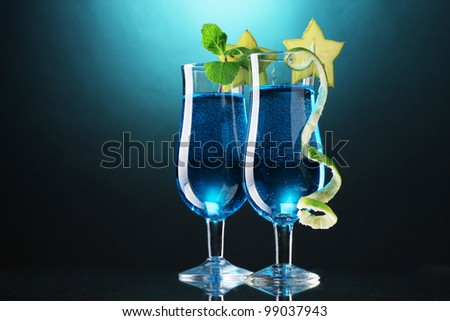 Blue cocktail in glasses on blue background - stock photo