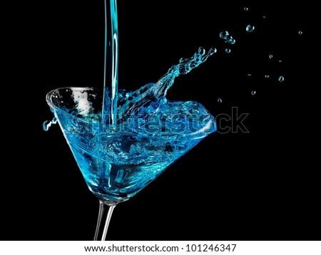 Blue cocktail splash in martini glass - stock photo