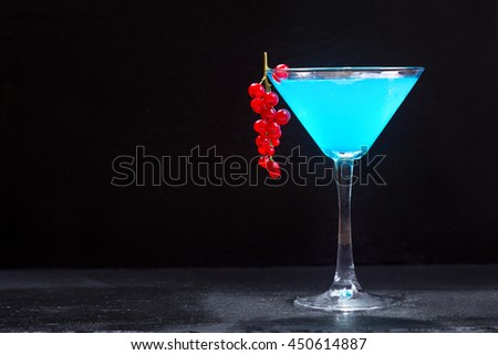 blue cocktail with red currant on dark background - stock photo