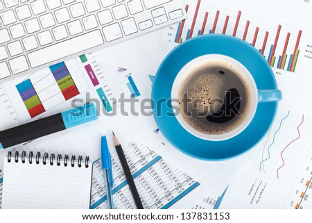 Blue coffee cup on financial papers, computer and office supplies - stock photo