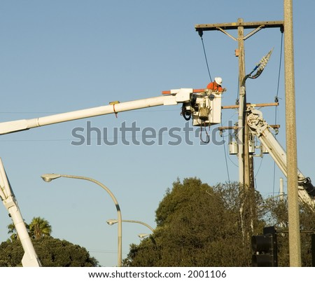 blue collar utility pole worker installing new wires and cables on power utility pole - stock photo
