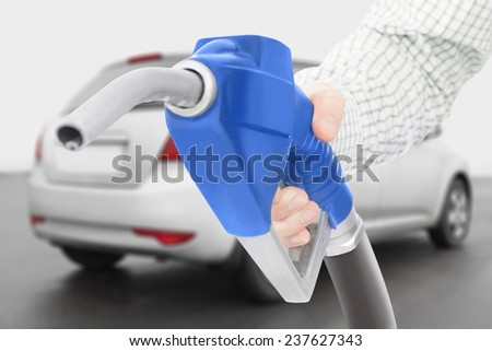 Blue color fuel pump gun with car on background - stock photo