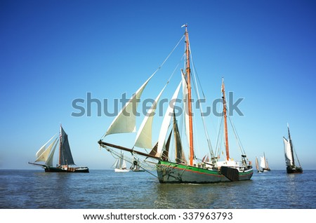 Blue color image of a fleet of traditional sailing ships on the ocean. - stock photo