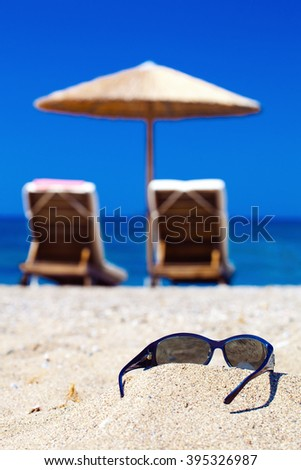 blue color of sea and sunglasses on sand. Focus on sunglasses - stock photo