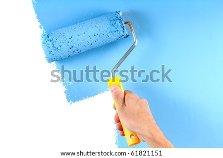 blue color painting wall with roller in hand - stock photo
