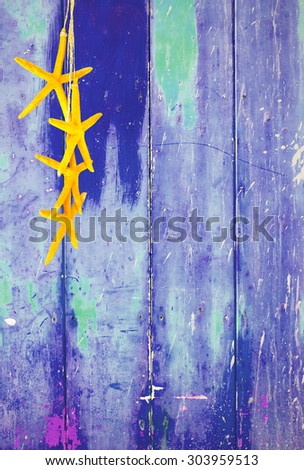 Blue colorful vintage background with shabby distressed grungy texture hippie style decorated with yellow sea stars hanging from a straw string.  - stock photo