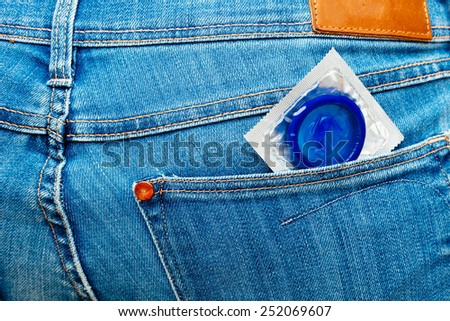 Blue condom in a jeans pocket. - stock photo