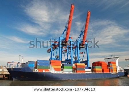 blue container ship unloading freight with two cranes - stock photo
