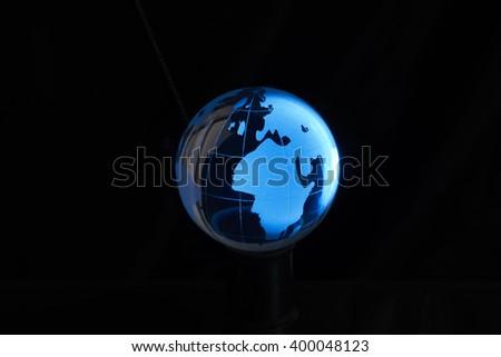 Blue crystal globe, isolated on black background. - stock photo