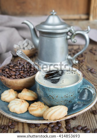 Blue cup of black coffee, cookies and coffee pot  surrounded by linen cloth, sugar pieces and coffee beans on old wooden table - stock photo