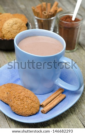 blue cup of cocoa with cinnamon and oatmeal cookies, vertical - stock photo