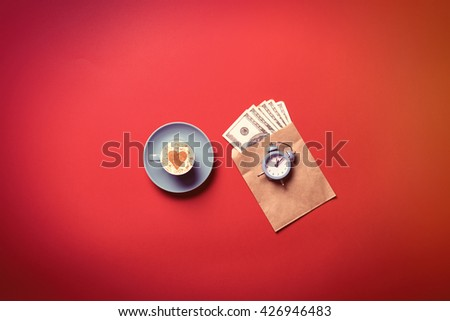 blue cup of coffee, clock and money in the envelope on the red background - stock photo