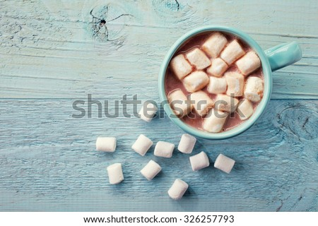 Blue cup of hot cocoa with marshmallows on blue wooden background - stock photo