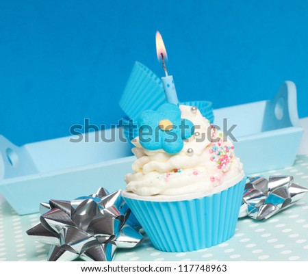 blue cupcake with whipped cream and candle for birthday party - stock photo