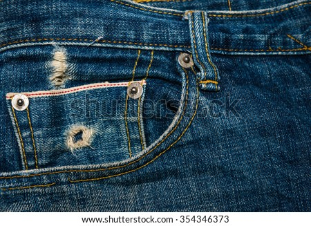 Blue denim jeans in dark color tear up surface condition present the old damaging fabric damaged detail of texture background. - stock photo