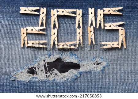 Blue denim jeans with the clothespin made from wood in the scene present the old denim look and old damaging fabric that shown detail of texture background and wording 2015 from clothespin.  - stock photo