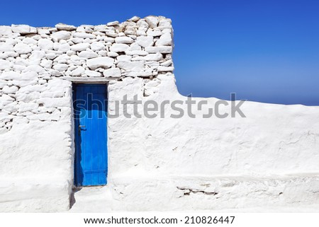 Blue door in whitewashed wall on Mykonos, Greece. - stock photo