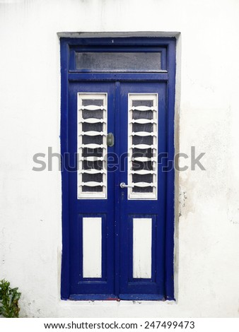 Blue door on white wall - stock photo
