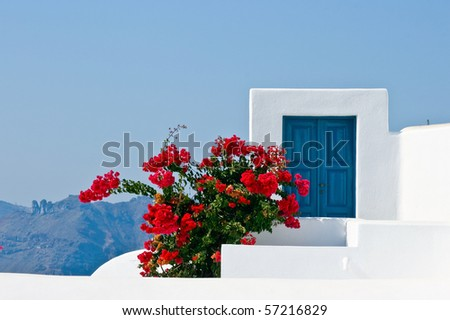 Blue door with red flowers in Santorini, Greece - stock photo