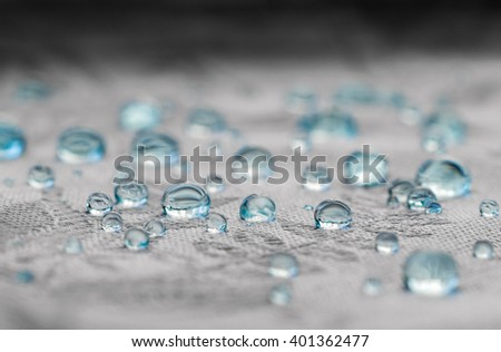 Blue drops in macro view on textile fabric fibers - stock photo