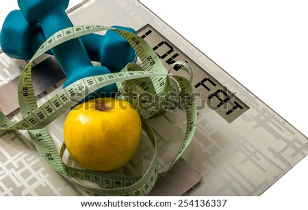 Blue dumbbells and apple and measure tape on weighing machine with sign low fat - stock photo