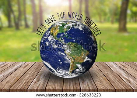 Blue Earth on wooden table and blurred green forest background. Elements of this image furnished by NASA - stock photo