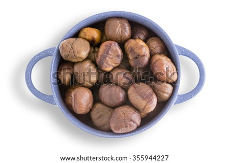 Blue earthenware bowl full of fresh roasted chestnuts harvested during autumn and fall for a tasty healthy seasonal snack viewed from overhead on a white background - stock photo