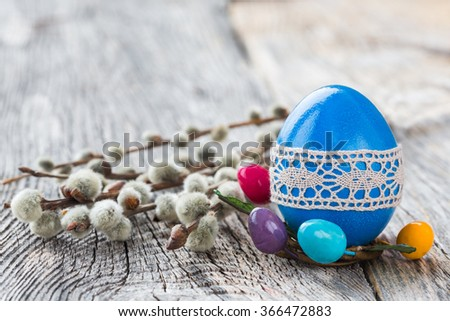 Blue Easter egg decorated with lace and willow branch on wooden background. Selective focus, copy space - stock photo