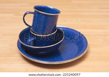 Blue enamel plates, bowl;s and mugs stacked - stock photo