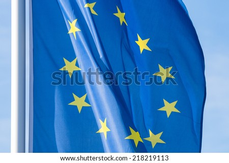 blue european flag with twelve yellow stars blowing in the wind  - stock photo
