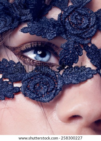 Blue eye closeup.Beautiful fashion girl with arrow make up. Closeup female eye with beautiful fashion bright makeup,lace on the face - stock photo