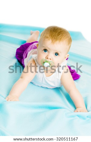 blue-eyed baby girl with pacifier crawling on the blue coverlet - stock photo