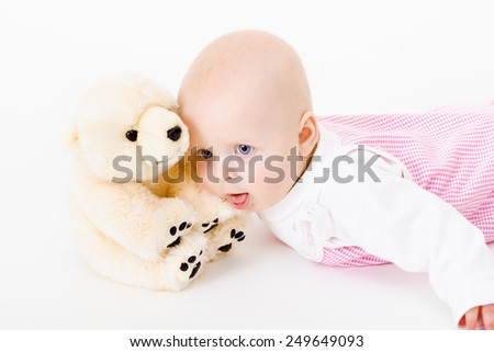 blue-eyed baby with a soft toy. studio photo. nausea. humor - stock photo