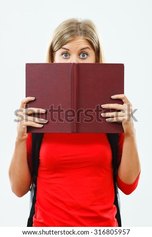 Blue eyed female student is hiding behind a book.Student hiding behind book - stock photo