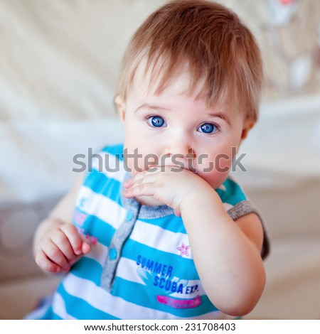 Blue-eyed little girl holding the hand in the mouth - stock photo