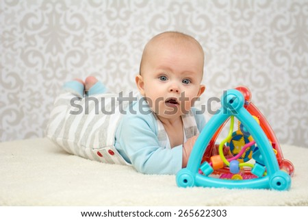 Blue eyes baby girl lying on belly on soft surface , playing with colourful toy and looking at the camera - stock photo
