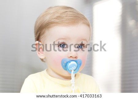 Blue eyes baby with pacifier at home - stock photo