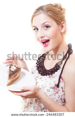 Blue eyes beautiful blond young woman eating large chocolate piece of cake happy looking at camera on white background portrait - stock photo