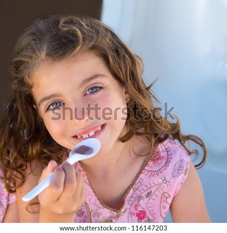 Blue eyes kid girl eating breakfast with spoon portrait - stock photo